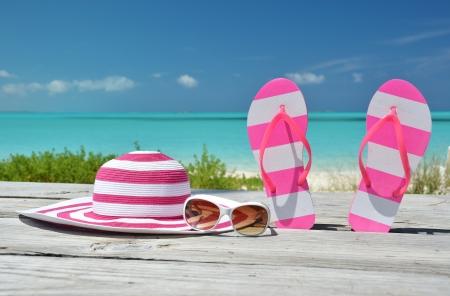 Hut, Sonnenbrille und Flip-Flops gegen Ozean. Exuma, Bahamas
