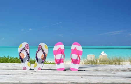 Women s shoes: Two pairs of flip-flops against ocean. Exuma, Bahamas