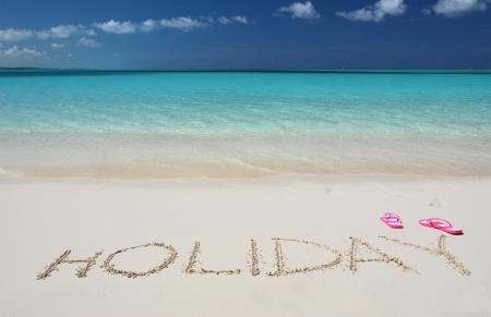 HOLIDAY writing on the sandy beach of Exuma, Bahamas photo