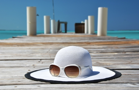 brim: Hat and sunglasses on the wooden jetty. Exuma, Bahamas