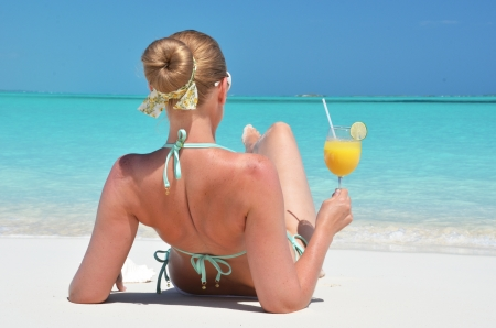 Girl with a glass of orange on the beach of Exuma, Bahamas photo
