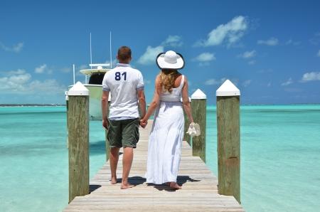 Couple on a wooden jetty. Exuma, Bahamas photo