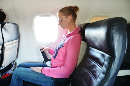 airplanes: Girl fastening her seat belt