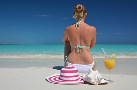 Girl with a glass of orange juice on the beach of Exuma, Bahamas Stock Photo