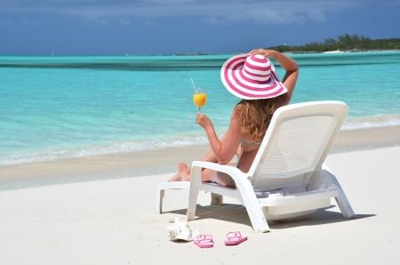 sea bed: Girl with a glass of orange juice on the beach of Exuma, Bahamas Stock Photo