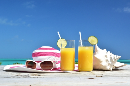 Orange juice, hat, sunglasses and conch on the tropical beach. Exuma, Bahamas Stock Photo