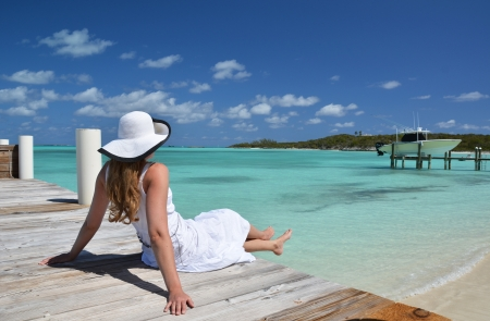 brim: Girl on the wooden jetty looking to the ocean  Exuma, Bahamas