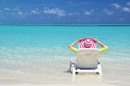 Mädchen in einem gestreiften Hut auf dem Strand von Exuma, Bahamas