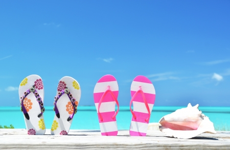 sandy feet: Two pairs of flip-flops and a shell against Atlantic. Exuma, Bahamas