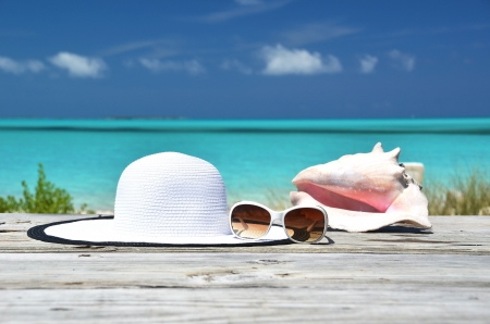 Sunglasses, hat and conch against ocean. Exuma, Bahamas Stock Photo