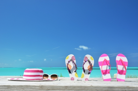 sandy feet: Hat, sunglasses and flip-flops on the beach of Exuma, Bahamas Stock Photo