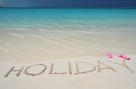 sand writing: HOLIDAY writing on the sandy beach  Stock Photo