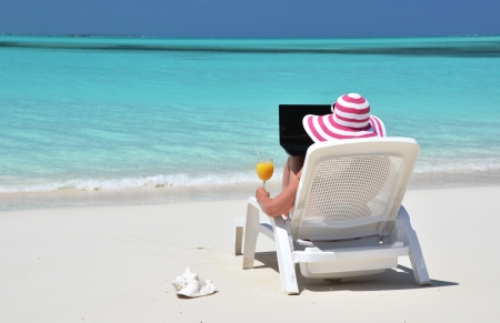 coolie hat: Girl with a laptop on the tropical beach. Exuma, Bahamas Stock Photo