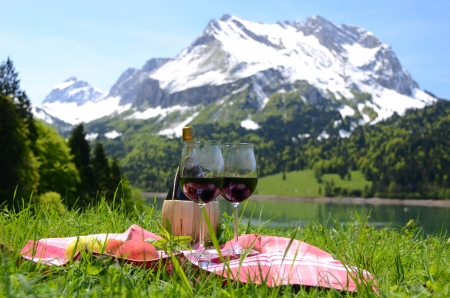 Wine and fruits served at a picnic in Alpine meadow. Switzerland photo