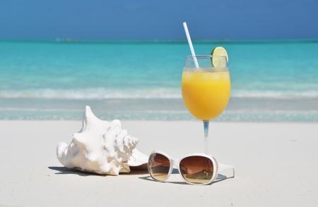 caribbean food: Orange juice and sunglasses on the beach. Exuma, Bahamas Stock Photo