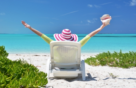 coolie hat: Girl with a shell on the sunbed looking to the ocean. Exuma, Bahamas