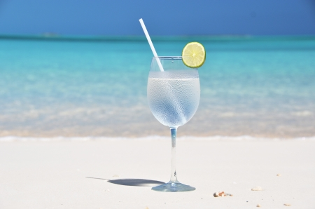 lemon water: Glass of water on the tropical beach Stock Photo