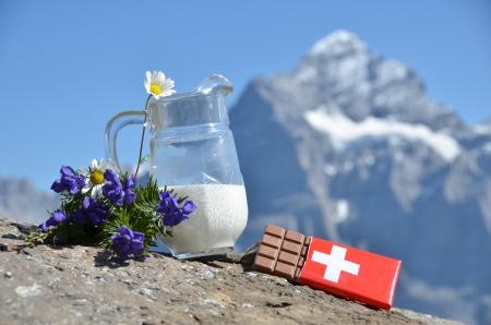 Swiss chocolate and jug of milk against mountain peak. Switzerland photo