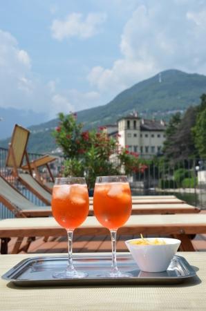 lake como: Traditional Italian Spritz cocktail against lake Como, Italy Stock Photo