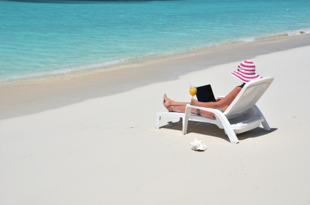 coolie hat: Girl with a laptop on the tropical beach  Exuma, Bahamas