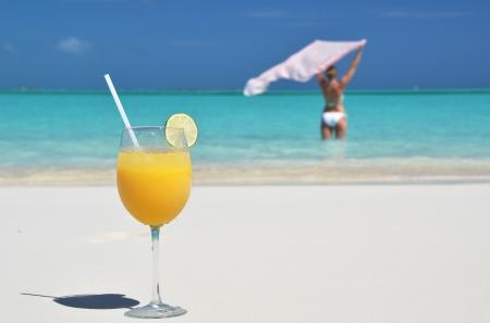 Glass of orange juice on the sandy beach of Exuma, Bahamas photo
