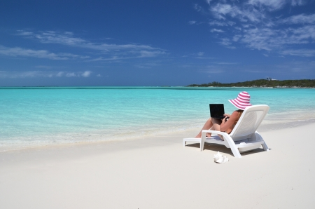 Girl with a laptop on the tropical beach  Exuma, Bahamas