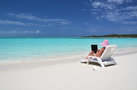 Mädchen mit einem Laptop auf dem tropischen Strand Exuma, Bahamas