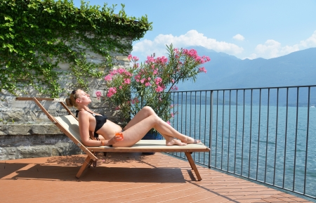 Young woman sunbathing at the Como lake photo
