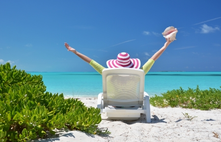 coolie hat: Girl with a shell on the sunbed looking to the ocean  Exuma, Bahamas Stock Photo