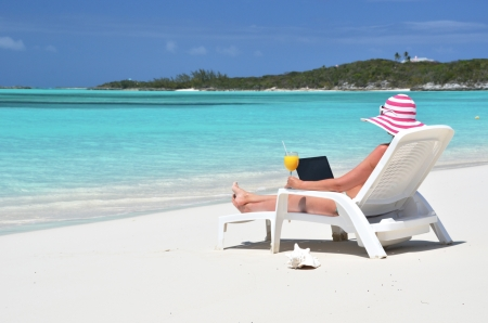 Girl with a laptop on the tropical beach. Exuma, Bahamas  photo