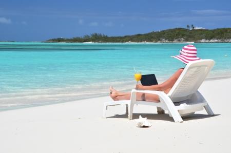 coolie hat: Girl with a laptop on the tropical beach. Exuma, Bahamas