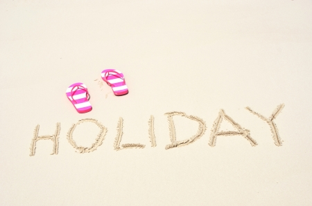 sandy feet: HOLIDAY writing on the sandy beach Stock Photo