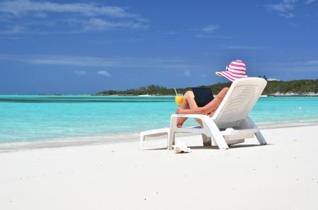silla playa: Chica con un ordenador port�til en la playa tropical
