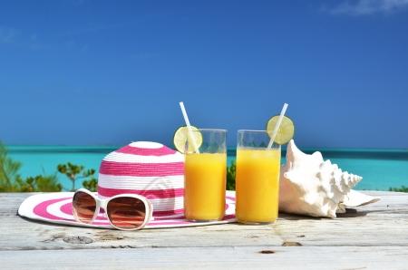 Gafas de sol, sombrero y jugo de naranja