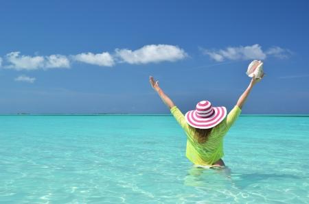 brim: Girl with a seashell in the turqouise water of Atlantic. Exuma, Bahamas Stock Photo