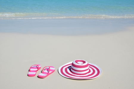 sandy feet: Flip-flops and hat on the beach