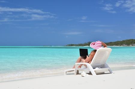 열 대 해변에 노트북을 가진 여자입니다. 조지 타운, 바하마