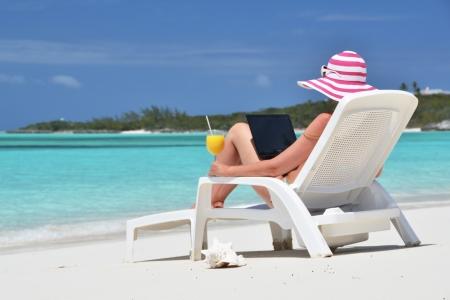 Mädchen mit einem Laptop auf der tropischen Strand. Exuma, Bahamas