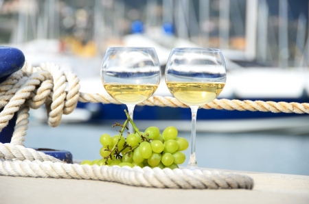 Pair of wineglasses and grapes against the yacht pier of La Spezia, Italy  Stock Photo