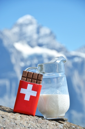Swiss chocolate and jug of milk against mountain peak. Switzerland  Stock Photo