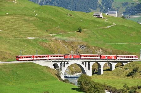 ancient pass: SWITZERLAND - SEP 16: Glacier Express of Matterhorn-Gotthard railway passing a bridge at Furka pass on September 16, 2012 in Switzerland.  Editorial