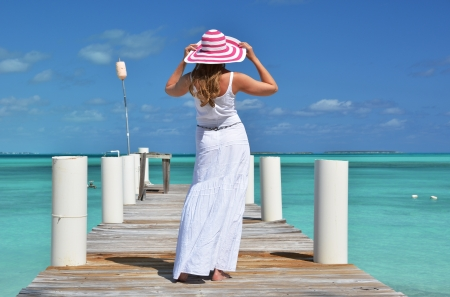 brim: Girl on the wooden jetty looking to the ocean. Exuma, Bahamas
