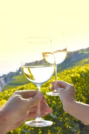 Dos manos sosteniendo wineglases contra viñedos en la región de Lavaux, Suiza
