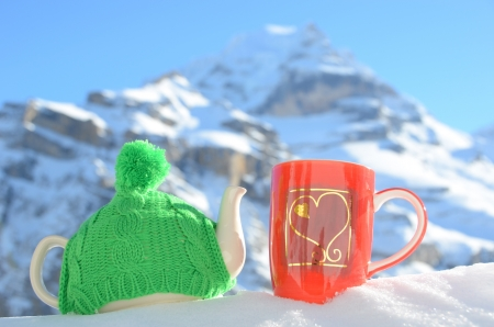 Tea pot in the knitted cap and red cup with a heart in the snow  photo