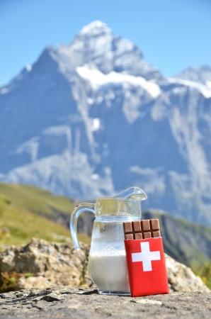 chocolate peak: Swiss chocolate and jug of milk against mountain peak. Switzerland  Stock Photo