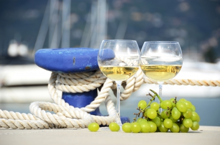 mooring: Pair of wineglasses and grapes against the yacht pier of La Spezia, Italy  Stock Photo