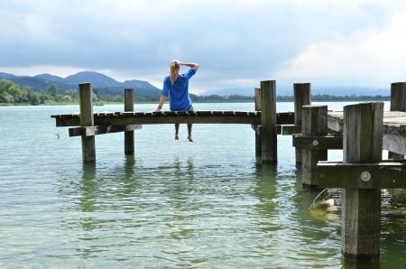 Girl on the wooden jetty. Switzerland photo