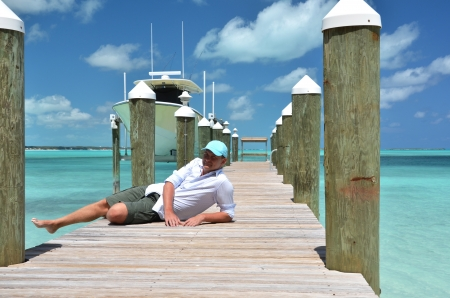 Manl on the wooden jetty. Great Exuma, Bahamas photo
