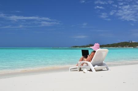 Girl with a laptop on the tropical beach. Exuma, Bahamas  photo