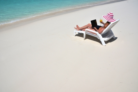 Girl with a laptop on the tropical beach. Exuma, Bahamas  Stock Photo - 22015259